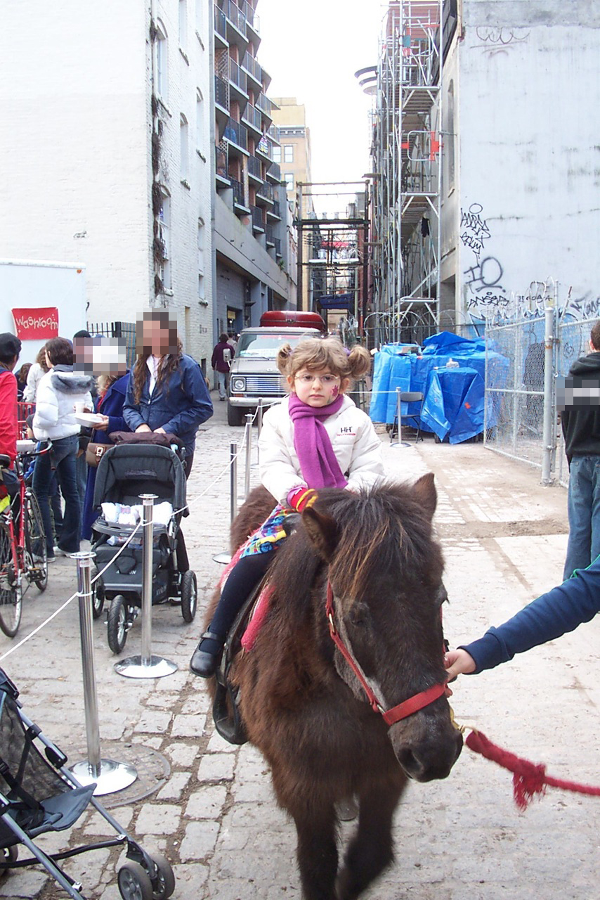 sad child on pony in an alley